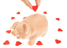 Cute piglet-piggy bank for the collection of hearts. Royalty Free Stock Images