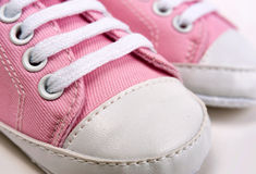 Cute pink baby girl sneakers close up on gray Royalty Free Stock Photography