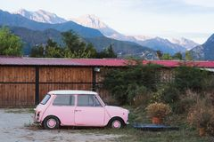 Pink car near the fence. Cute pink car parked near the fence beyond which mountains are seen Royalty Free Stock Images