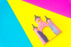 Cute pink Castle toy on blue, yellow and pink background stock photo