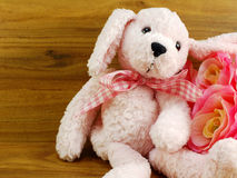 Cute pink dog doll and artificial rose flower decoration on wooden background Stock Photography
