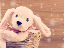 Cute pink dog doll in the basket with wooden background with vintage filter color. Pink dog doll in the basket with wooden background with vintage filter color Royalty Free Stock Images