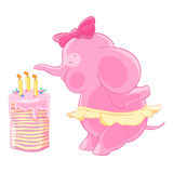 Cute pink elephant girl with bow and the skirt blows out candles on a birthday cake. Makes a wish. Stock Images