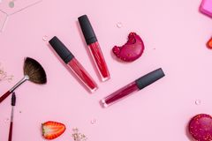 Cute pink flat layand lipstick with lip gloss in the center. Glamorous style stock photos