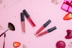 Cute pink flat layand lipstick with lip gloss in the center. Glamorous style stock image