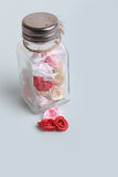 Cute pink, red, white and cream flowers in a glass jar on a blue background Stock Images