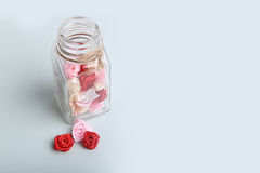 Cute pink, red, white and cream flowers in a glass jar on a blue background Stock Photo