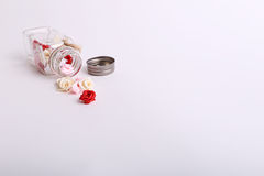Cute pink, red, white and cream flowers in a glass jar on a White background Stock Photos