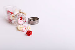 Cute pink, red, white and cream flowers in a glass jar on a White background Royalty Free Stock Image