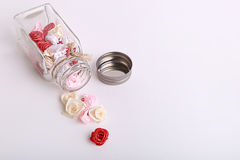 Cute pink, red, white and cream flowers in a glass jar on a White background Stock Photo