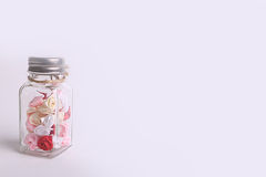 Cute pink, red, white and cream flowers in a glass jar on a White background Royalty Free Stock Images