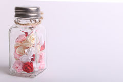 Cute pink, red, white and cream flowers in a glass jar on a White background Stock Photography