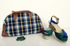 Cute plaid bag with matching sandals. Green with brown tartan bag and accessoris on white shelf Stock Images