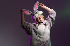 Happy and playful easter bunny girl. Cute and playful girl in a full body bunny suit with big ears. Dark colored background Stock Photo