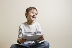 Cute playful happy child with digital tablet computer playing games. Stock Image