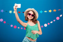 Cute playful little girl taking selfie with mobile phone Stock Image
