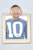 Cute playful man in trendy blinder sunglasses. Wearing a number 10 shirt smiling cheekily at the camera with his head through a vintage wooden picture frame Royalty Free Stock Photos