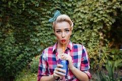 Cute playful pin-up girl drinking soda in the garden. In summer stock photos