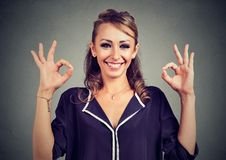 Cute playful young woman showing two ok signs over gray background royalty free stock image
