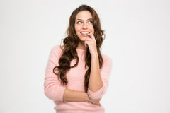 Cute playful young woman smiling and thinking Royalty Free Stock Photos