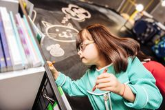 Cute pleasant girl with Down syndrome drawing cute cat on blackboard. Drawing cat. Cute pleasant dark-haired girl with Down syndrome drawing cute cat on royalty free stock image