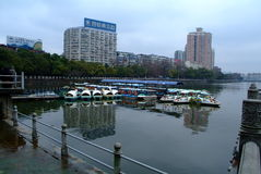 Cute pleasure boat. A row of boats docked at the lake. cute pleasure boat with background of city stock image