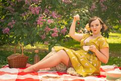 Cute plus size caucasian girl wearing a cute vintage yellow dress and enjoying a vacation in the summer Park on the green grass. c. Urvy pinup woman in retro royalty free stock images