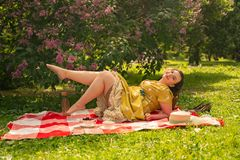 Cute plus size caucasian girl wearing a cute vintage yellow dress and enjoying a vacation in the summer Park on the green grass. c. Urvy pinup woman in retro royalty free stock photography