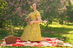 Cute plus size caucasian girl wearing a cute vintage yellow dress and enjoying a vacation in the summer Park on the green grass. c. Urvy pinup woman in retro stock photo