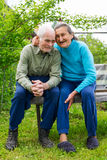 Cute 80 plus year old married couple posing for a portrait in their garden. Love forever concept.  stock photos