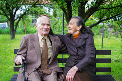 Cute 80 plus year old married couple posing for a portrait in their garden. Love forever concept.  Royalty Free Stock Images