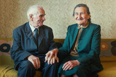 Cute 80 plus year old married couple posing for a portrait in their house. Love forever concept.  Royalty Free Stock Photography