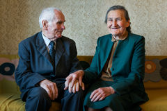 Cute 80 plus year old married couple posing for a portrait in their house. Love forever concept Stock Photo
