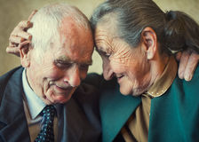 Cute 80 plus year old married couple posing for a portrait in their house. Love forever concept