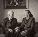 Cute 80 plus year old married couple posing for a portrait in their house. Love forever concept. Royalty Free Stock Photos