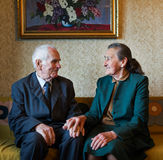 Cute 80 plus year old married couple posing for a portrait in their house. Love forever concept. Stock Image