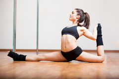 Cute pole dancer stretching. Beautiful young woman warming up and stretching during a pole dancing class Royalty Free Stock Image