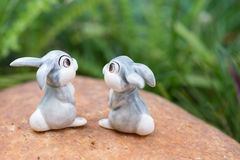 Cute porcelain rabbits looking at the green grass Royalty Free Stock Photo