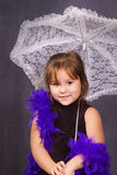 Cute Portrait. A four year old girl holding a lace umbrella getting her portrait done and wearing a feather boa Royalty Free Stock Images