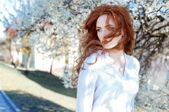 Cute portrait of a beautiful redhead girl with make-up and red lipstick in a white shirt in the garden among the blooming trees on Stock Photos