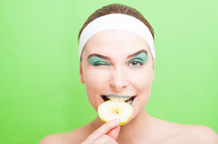Cute portrait of female bite a slice of apple Royalty Free Stock Photography