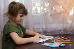 Cute portrait of little kid girl drawing by multi-colored pencils. concept of kids hobby or childhood royalty free stock photos