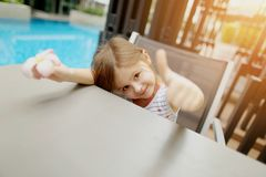 Cute portrait of little kid girl showing thumbs up or like on swimming pool. Sweet sunny portrait of little kid girl showing thumbs up or like on swimming pool stock photography