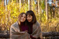 Cute portrait of mother and daughter in the autumn forest. royalty free stock image