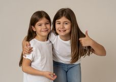 Two cute sisters playing together having fun posing and modeling stock image