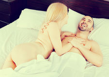 Cute positive beautiful happy couple having sex in bed Stock Photography