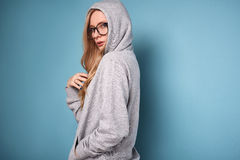 Cute positive blonde woman in gray hoodie and glasses. Portrait of a cute positive blonde woman in gray hoodie and glasses on bright background in studio Royalty Free Stock Image