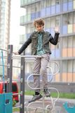 Cute positive boy teenager on the Playground in the city alone stock image