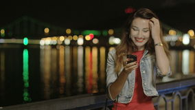 Cute Positive Female Texting and Messaging on the Phone at Night in the City with Street Lights and Cityscape Background stock video footage