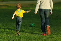 Cute positive kid with mother, playing happily with ball on green meadow royalty free stock photography